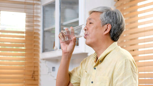 Senior asian man drinking water while standing by window in kitchen background, elderly retirement people and healthy lifestyles stock photo