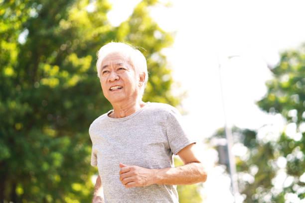 senior asian man exercising outdoors stock photo
