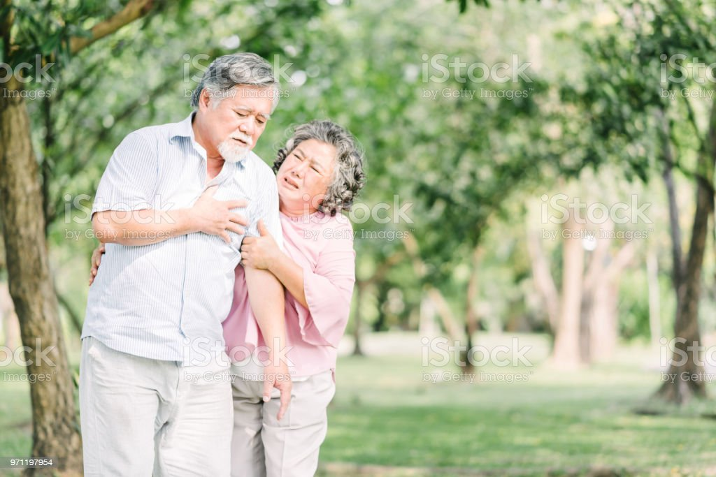 Senior Asian man feeling pain suffering from heart attack stock photo