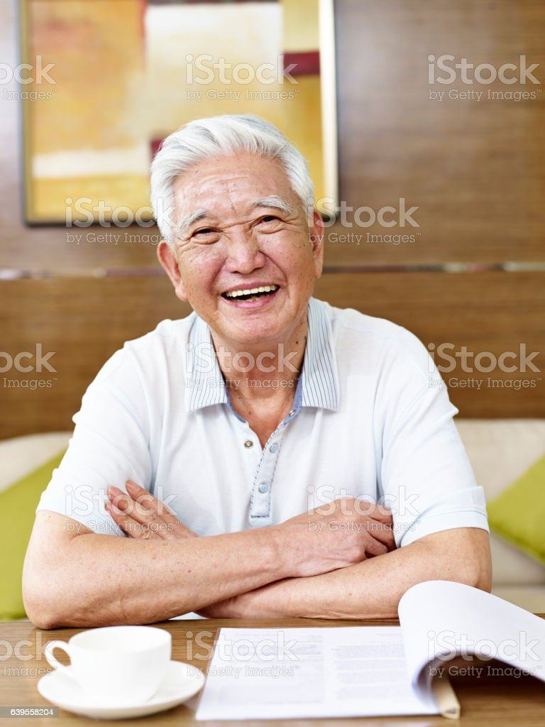 senior asian man reading in study room stock photo