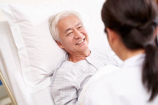senior asian patient talking to medical worker stock photo
