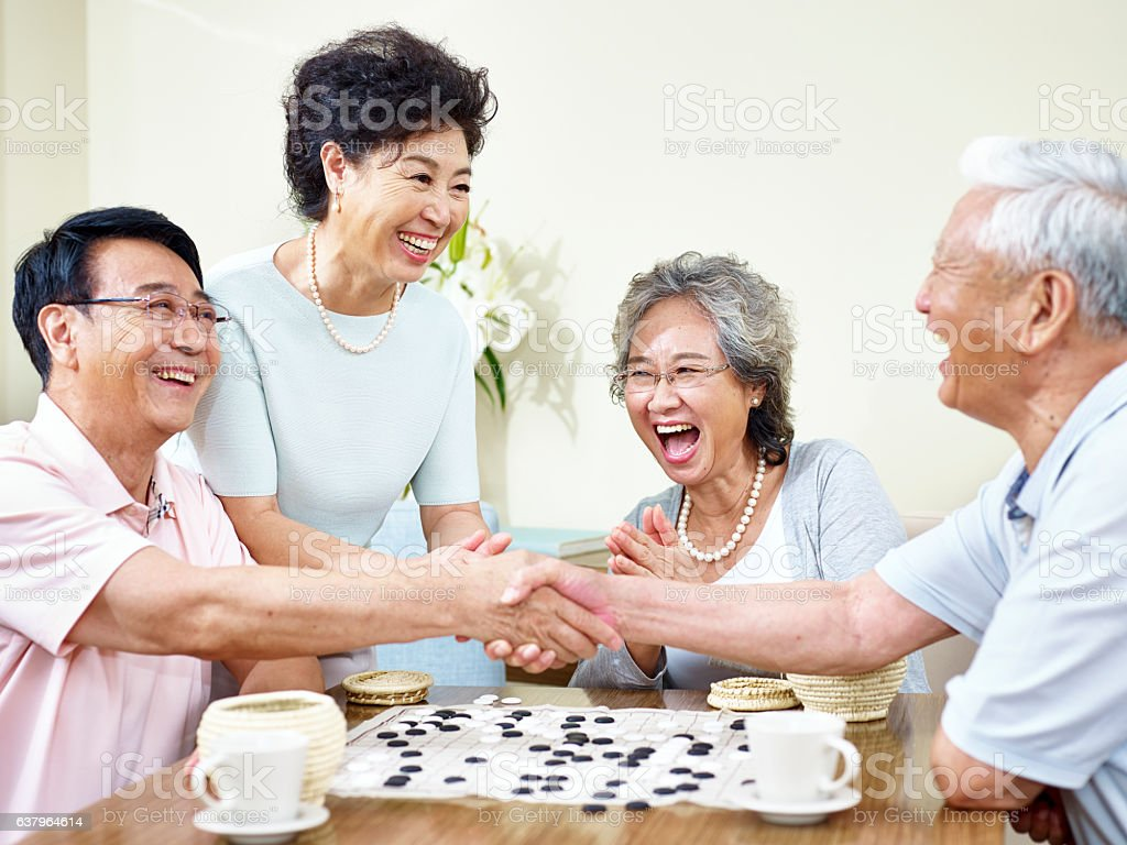 senior asian people playing weiqi stock photo