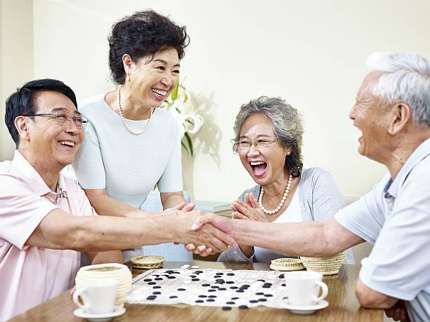 senior asian people playing weiqi stock photo