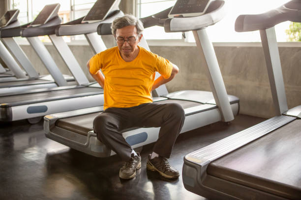 Senior asian sport man injury back pain  sitting on treadmill in fitness gym . elder male exercising , workout, training ,healthy ,Retirement ,older, with copy space stock photo