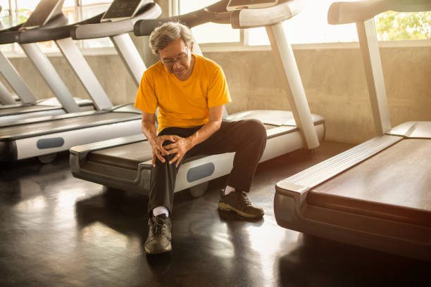 Senior asian sport man injury knee pain  sitting on treadmill in fitness gym . aged  suffering from Arthritis elder male exercising , workout, training ,healthy ,Retirement ,older, with copy space stock photo