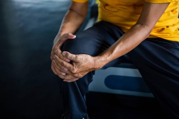 dor asiática sênior do joelho do ferimento do homem do esporte que senta-se na escada rolante na ginástica. idoso sofrendo de artrite homem idoso exercício, treino, treino, saudável, aposentadoria, mais velho, fechar-se - articulação humana - fotografias e filmes do acervo