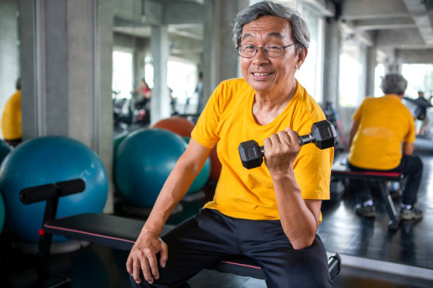 Senior asian sport man lifting dumbbells in fitness gym . elder male exercising ,  working out , training weights, healthy ,Retirement , older, looking camera stock photo