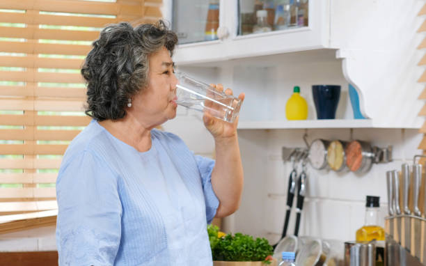 Senior asian woman drinking water while standing by window in kitchen background, people and healthy lifestyles stock photo