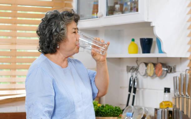 高級亞洲婦女喝水,而站在廚房背景的視窗,人和健康的生活方式 - 口渴 個照片及圖片檔