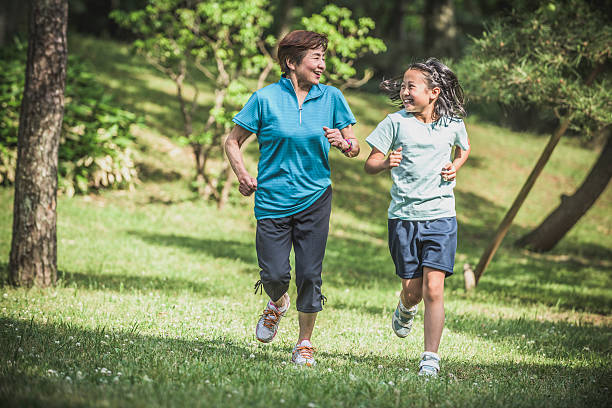 Senior Asian woman jogging with her granddaughter in park stock photo
