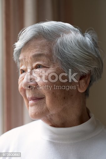 Content, confident, independent senior woman in her 90s, looking out window.  CreativeContentBrief 686998459: Senior Portrait