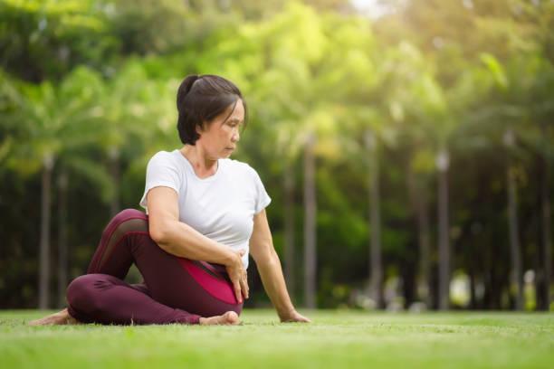 Senior Asian woman practicing yoga exercise outdoor in the morning. senior healthy lifestyle concept. stock photo