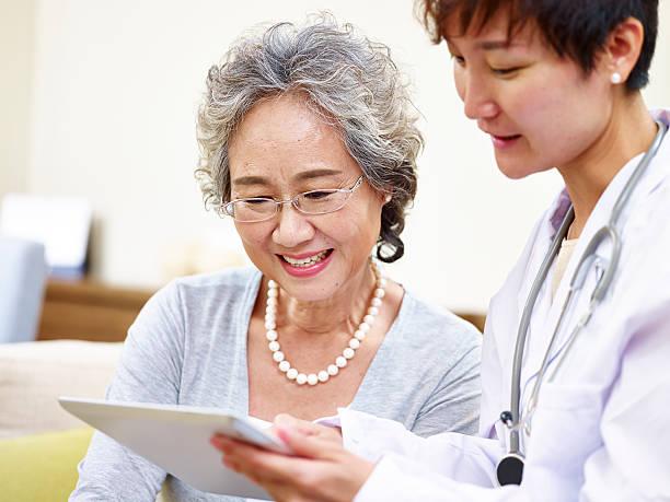 senior asian woman seeing family doctor - 高齢者介護 ストックフォトと画像
