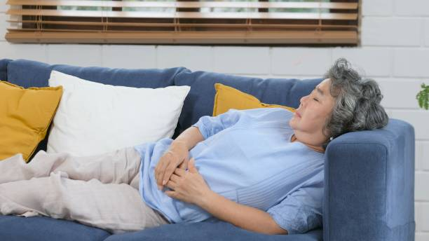 Senior asian woman sleeping on sofa, Asian female elderly take a nap at home living room in day, Old, retirement people lying and sleeping on sofa to take some rest stock photo