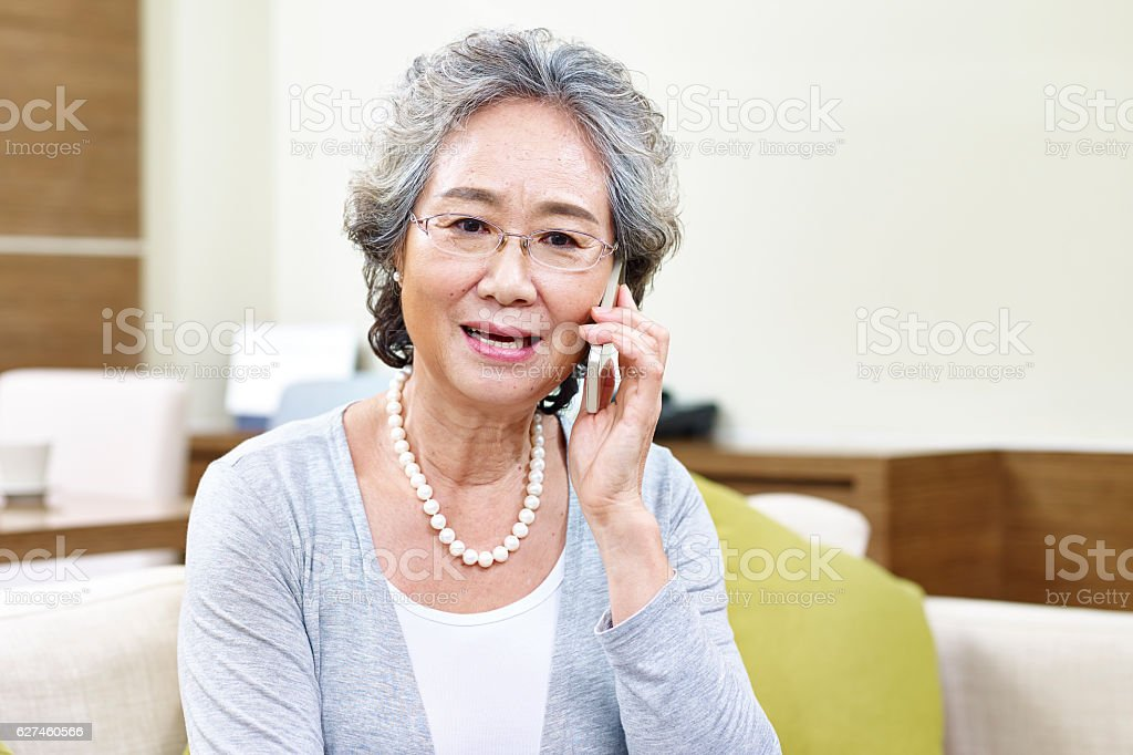 senior asian woman talking on cellphone stock photo