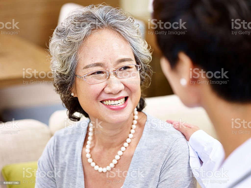 Senior asian woman talking to a doctor stock photo