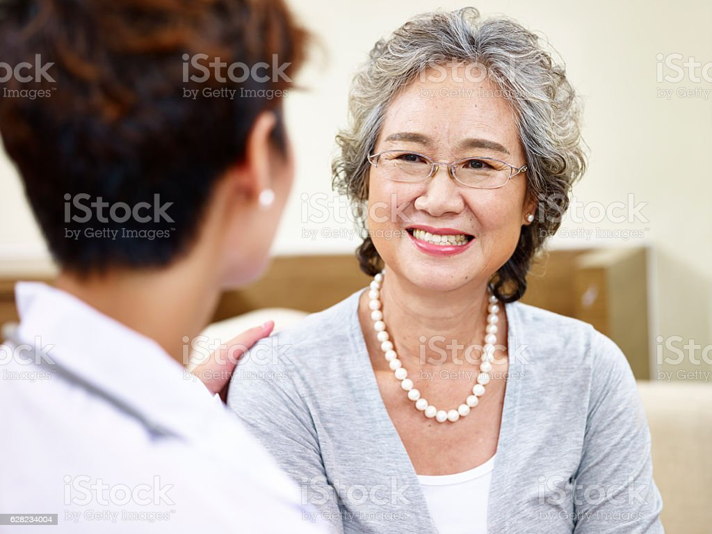 senior asian woman talking to family doctor stock photo
