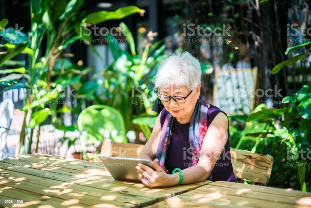 Senior Asian woman using a digital tablet stock photo