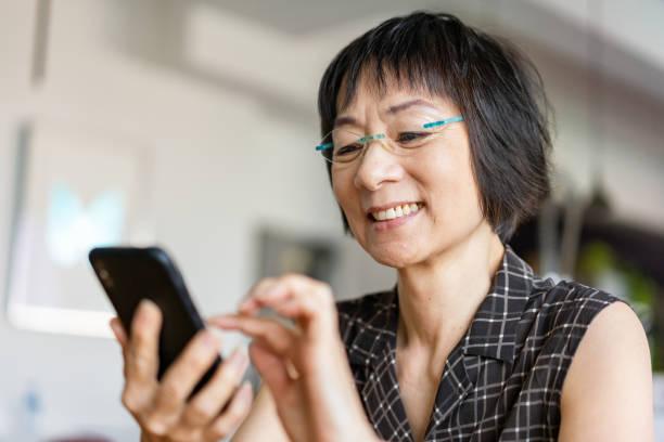 mujer asiática senior usando un teléfono inteligente - asian woman fotografías e imágenes de stock