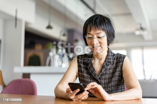 Senior Asian woman using a smartphone at home.