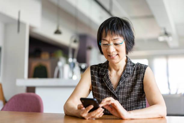 Senior Asian woman using a smartphone stock photo