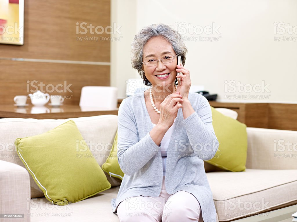 senior asian woman using cellphone stock photo