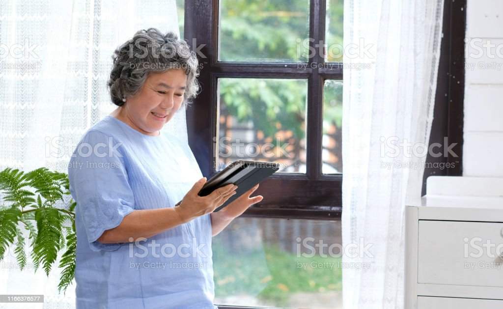 Senior asian woman using digital tablet computer at home background,...
