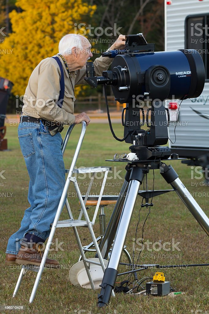 Senior astronomy hobbyist  aligns  telescope stock photo