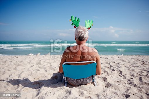 Senior caucasian ethnicity man relaxing on a beach chair at the beach during Summer Christmas and wearing reindeer hat. Picture was taken in Florida USA. He is 60 years old. Gray hair. He is sitting in front of the ocean looking at the waves and seagulls. It is a sunny day with beautiful blue sky.