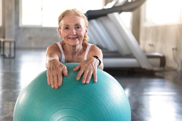 Senior bei Yoga Gym posiert Neigung auf ihren Ball lächelnd und glücklich.  älteren gesunden Lebensstil. – Foto