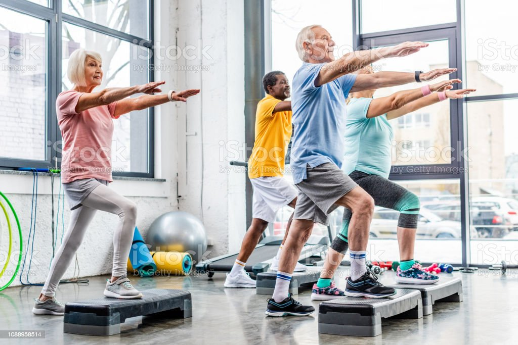 senior athletes synchronous exercising on step platforms at gym royalty-free stock photo