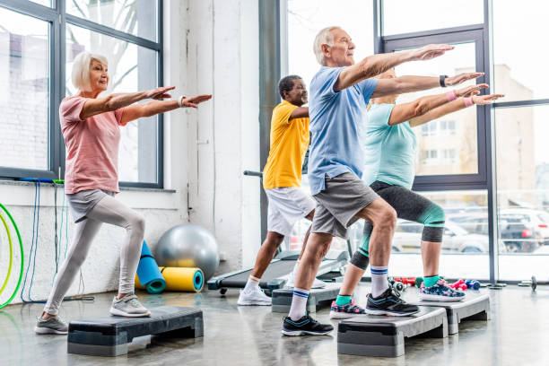 senior athletes synchronous exercising on step platforms at gym - idosos imagens e fotografias de stock