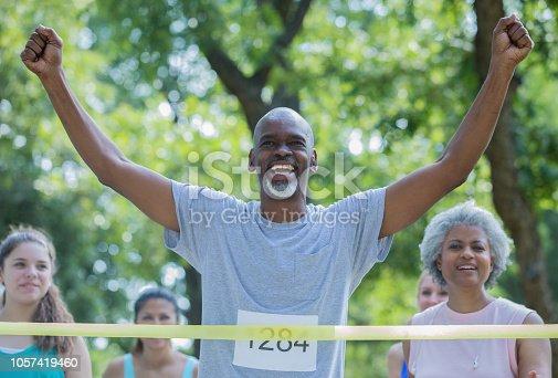 istock Senior athletic man celebrating crossing finish line during marathon race 1057419460