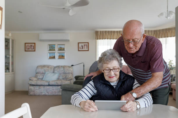 Senior Australian Couple Learning To Use Digital Tablet stock photo