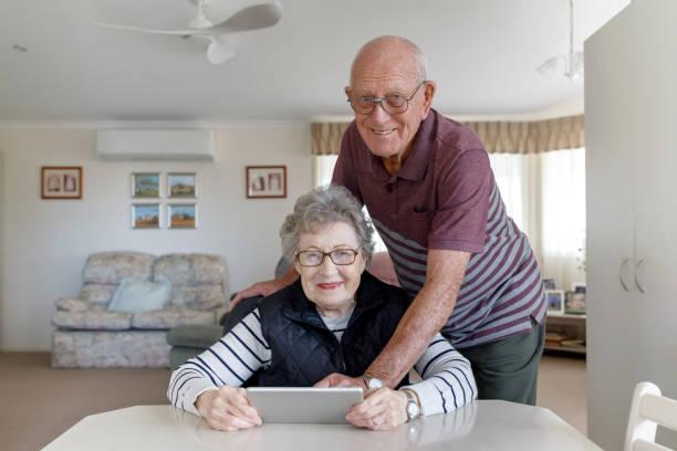 Senior Australian par lära sig använda Digital Tablet bildbanksfoto