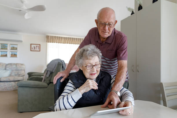 Senior Australian Couple Learning To Use Digital Tablet stock photo