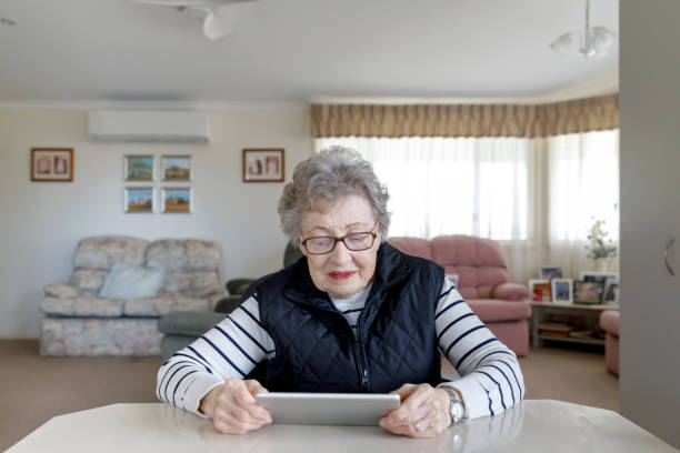 Senior Australian Woman Learning To Use Digital Tablet stock photo