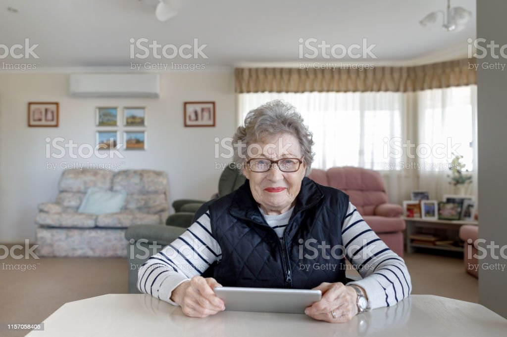 Portrait Of Senior Australian Woman Learning To Use Digital Tablet...
