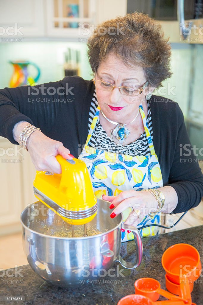 Senior Baking series-adding the dry ingredients royalty-free stock photo