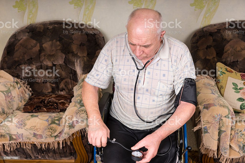 Senior Bald Man Checking his Blood Pressure Alone stock photo