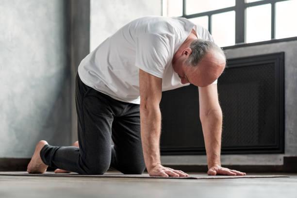 Senior bald yogi men practices yoga asana marjariasana or cat-cow pose stock photo