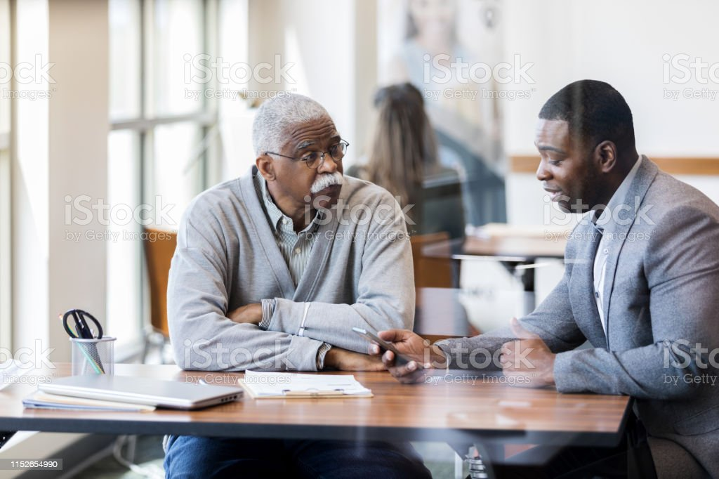 African American senior man talks with a male bank officer. The bank...