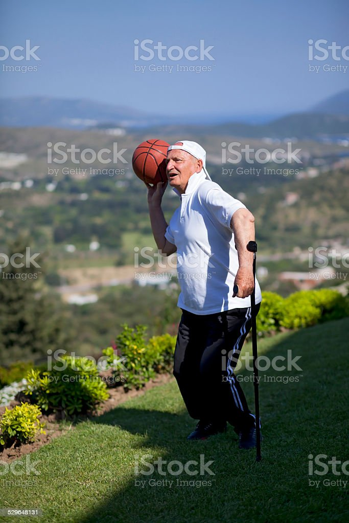 Senior basketball player with walking stick stock photo