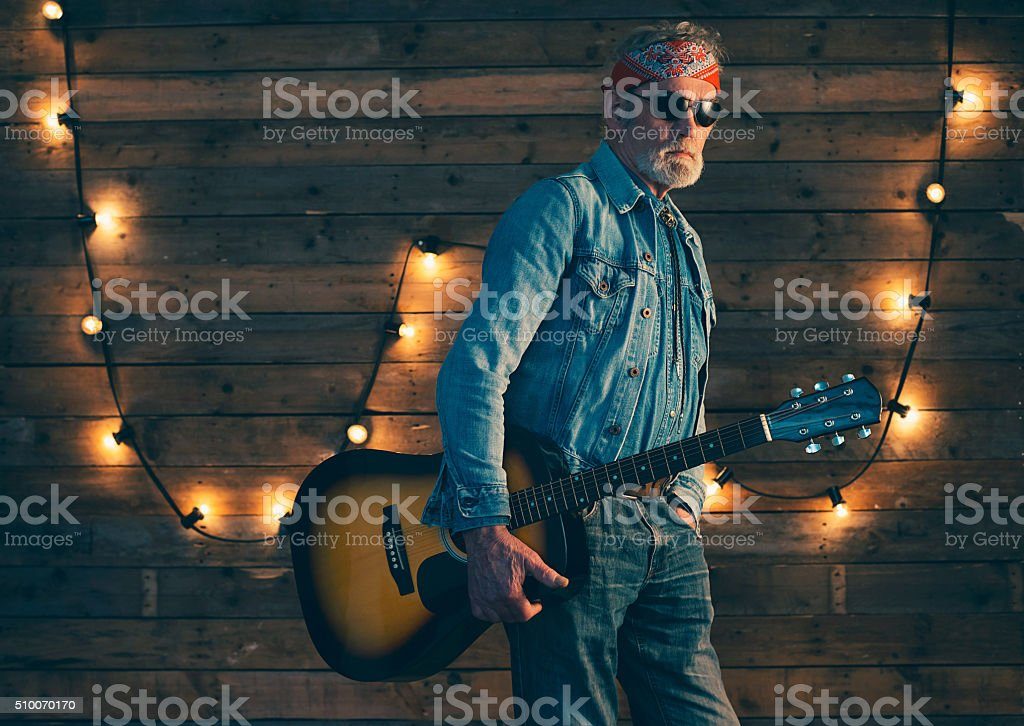 Senior bearded guitarist holding guitar standing in front wooden wall. stock photo