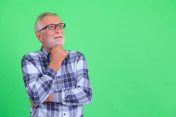 Senior bearded hipster man thinking and looking up stock photo