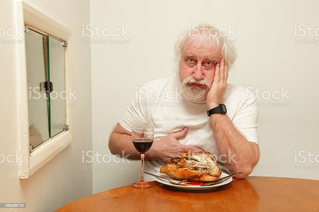 senior bearded male with indigestion after eating roast chicken stock photo