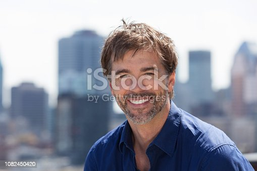 637538262istockphoto Senior bearded man portrait on a city background 1082450420