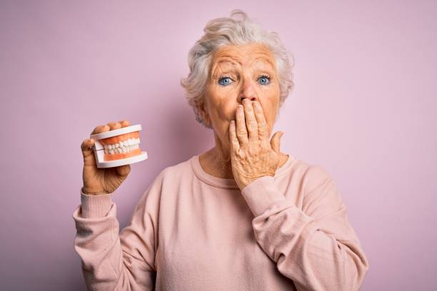Senior beautiful grey-haired woman holding plastic denture teeth over pink background cover mouth with hand shocked with shame for mistake, expression of fear, scared in silence, secret concept stock photo