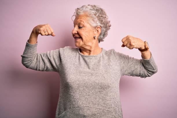 femme de beauté aîné utilisant le t-shirt occasionnel restant au-dessus du fond rose isolé affichant des muscles de bras souriant fier. concept de remise en forme. - seulement des femmes seniors photos et images de collection