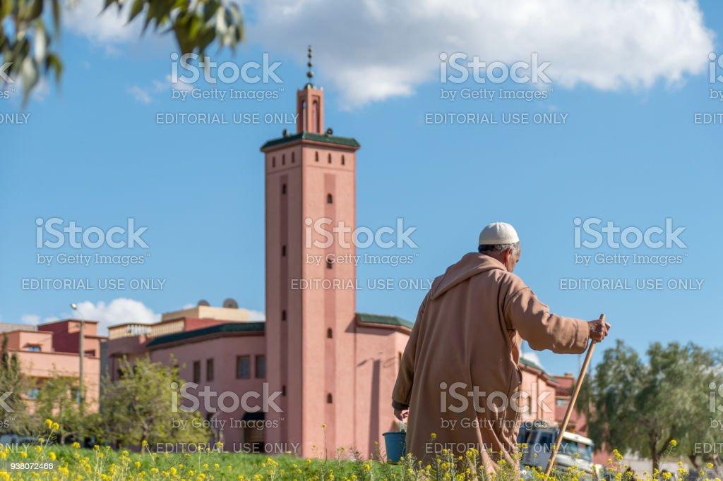 Senior Berber man walks past a Mosque in a field in Morroco stock photo